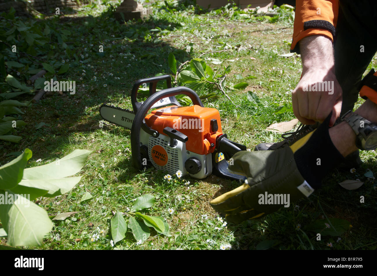 Putting chain back on stock photos putting chain back on stock man in full protective stihl clothing putting chainsaw gloves on before operating his power tool keyboard keysfo Choice Image