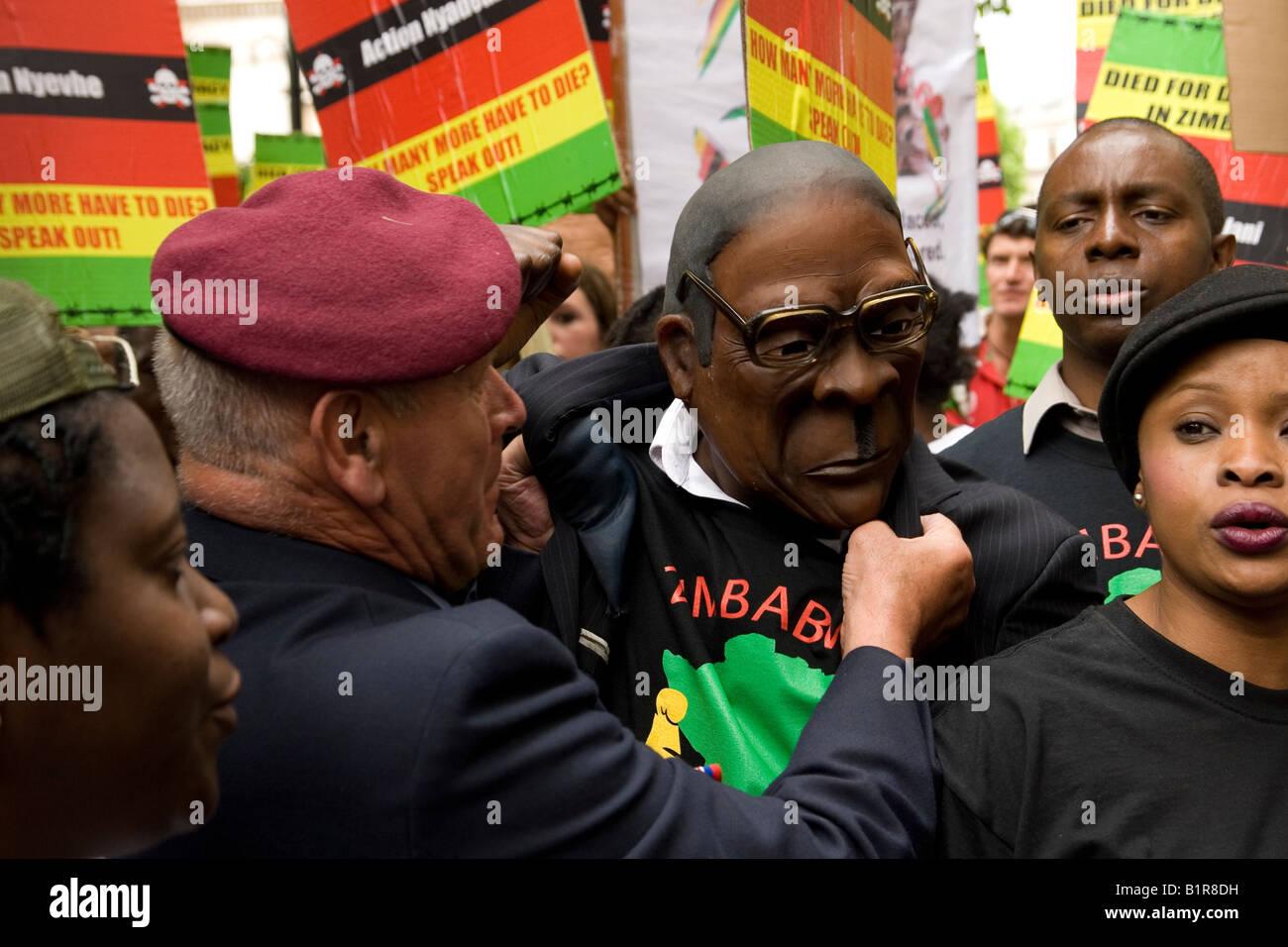 Anti Mugabe protesters grab man in Mugabe mask outside South Africa House London - Stock Image
