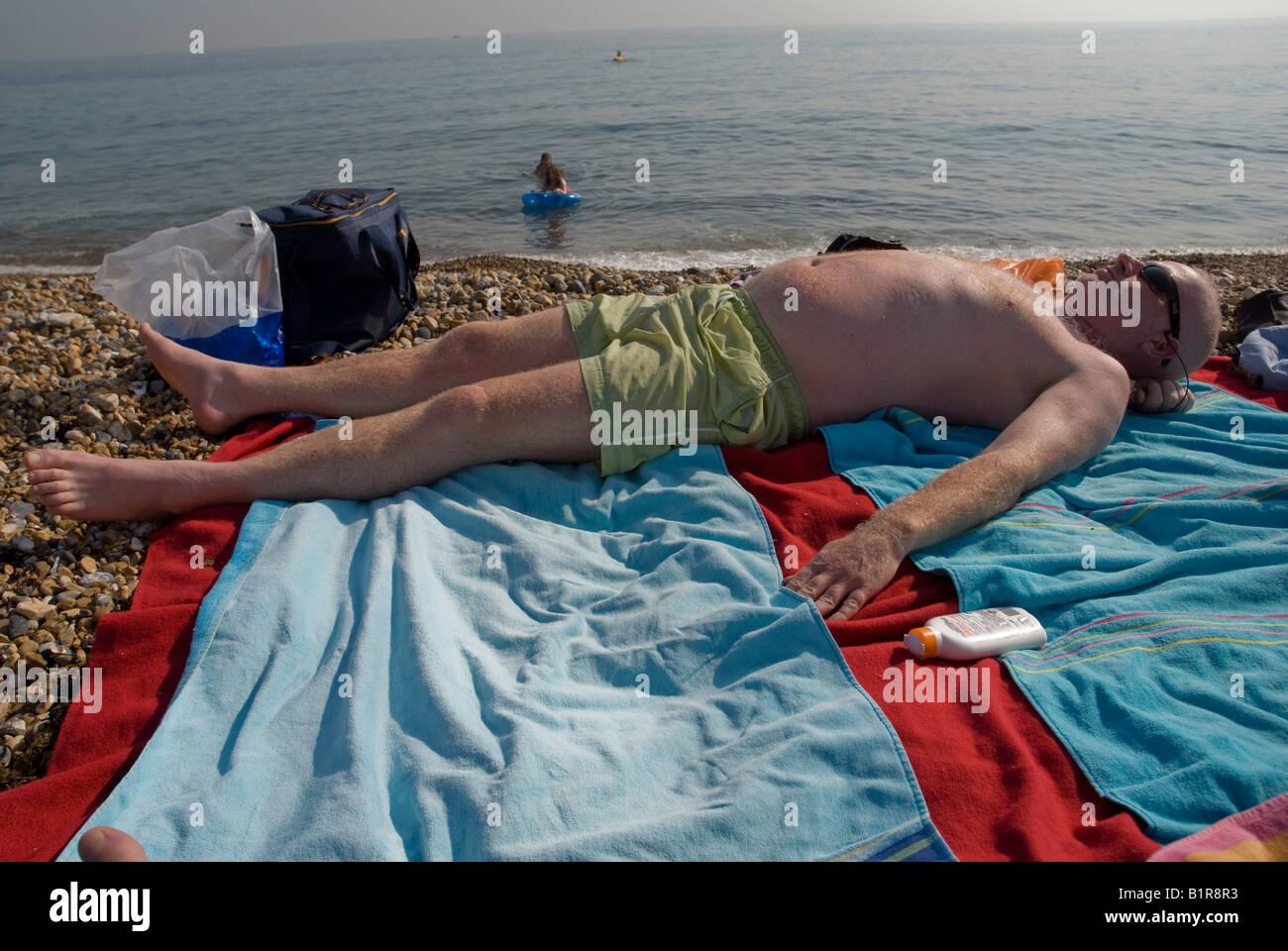 A man sunbathes on the beach at Salt Dean Sussex near Brighton - Stock Image