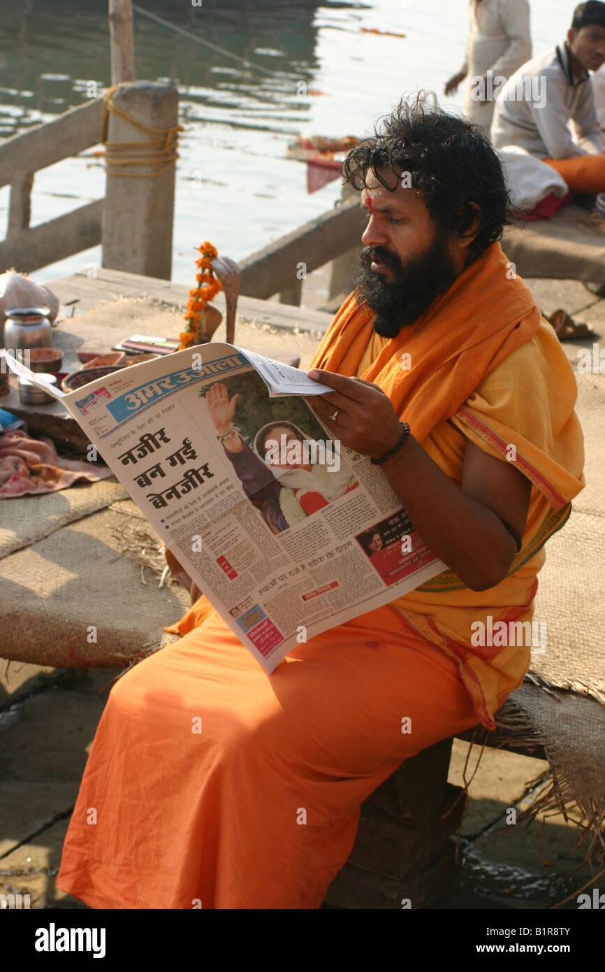Sadhu reading newspaper in Varanasi the morning after Benazir Bhutto's assasination - Stock Image