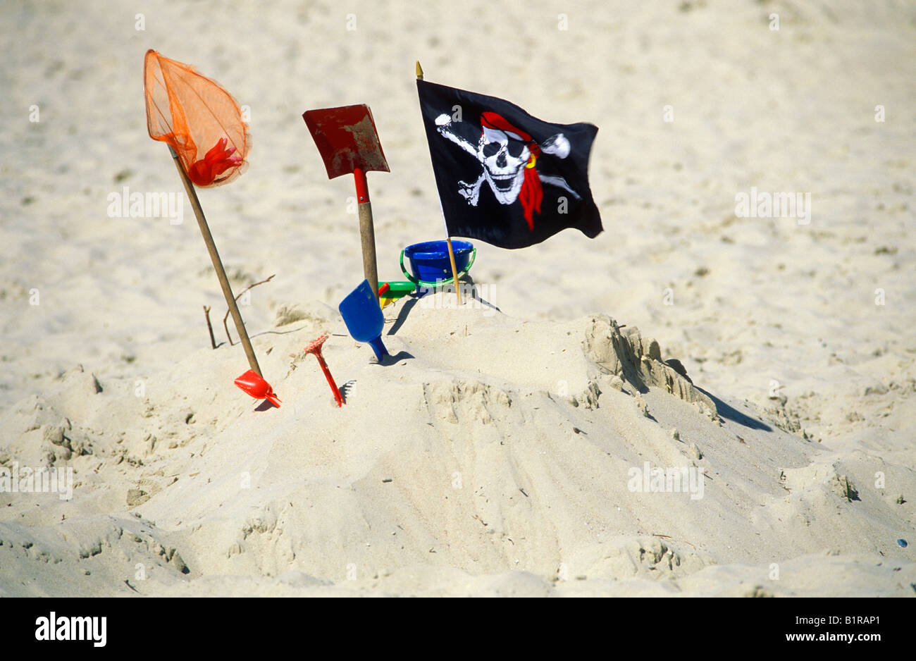 sand toys and pirate´s flag at a beach - Stock Image