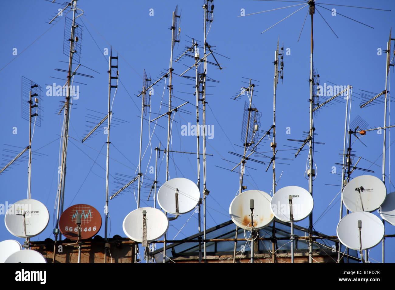 tv aerials and satellite dishes on rooftop Stock Photo
