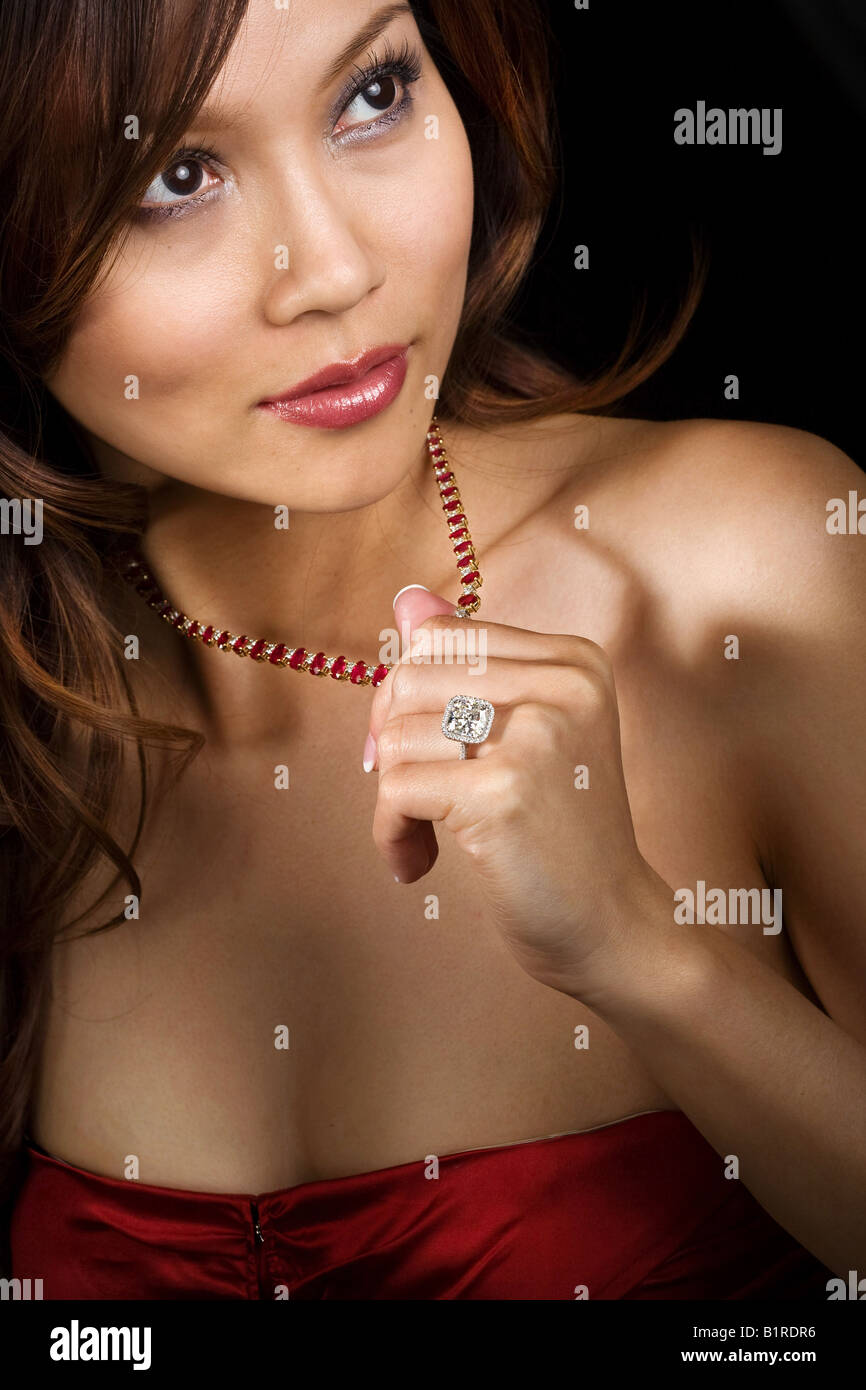 A beautiful woman wearing a diamond ring and rhinestone studded necklace. - Stock Image