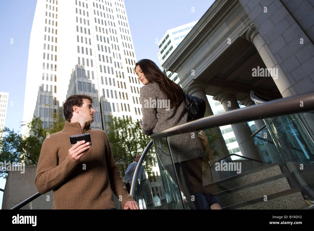 A young man and woman pass each other on a stairwell in a metropolitan area carrying hand held devices. - Stock Image