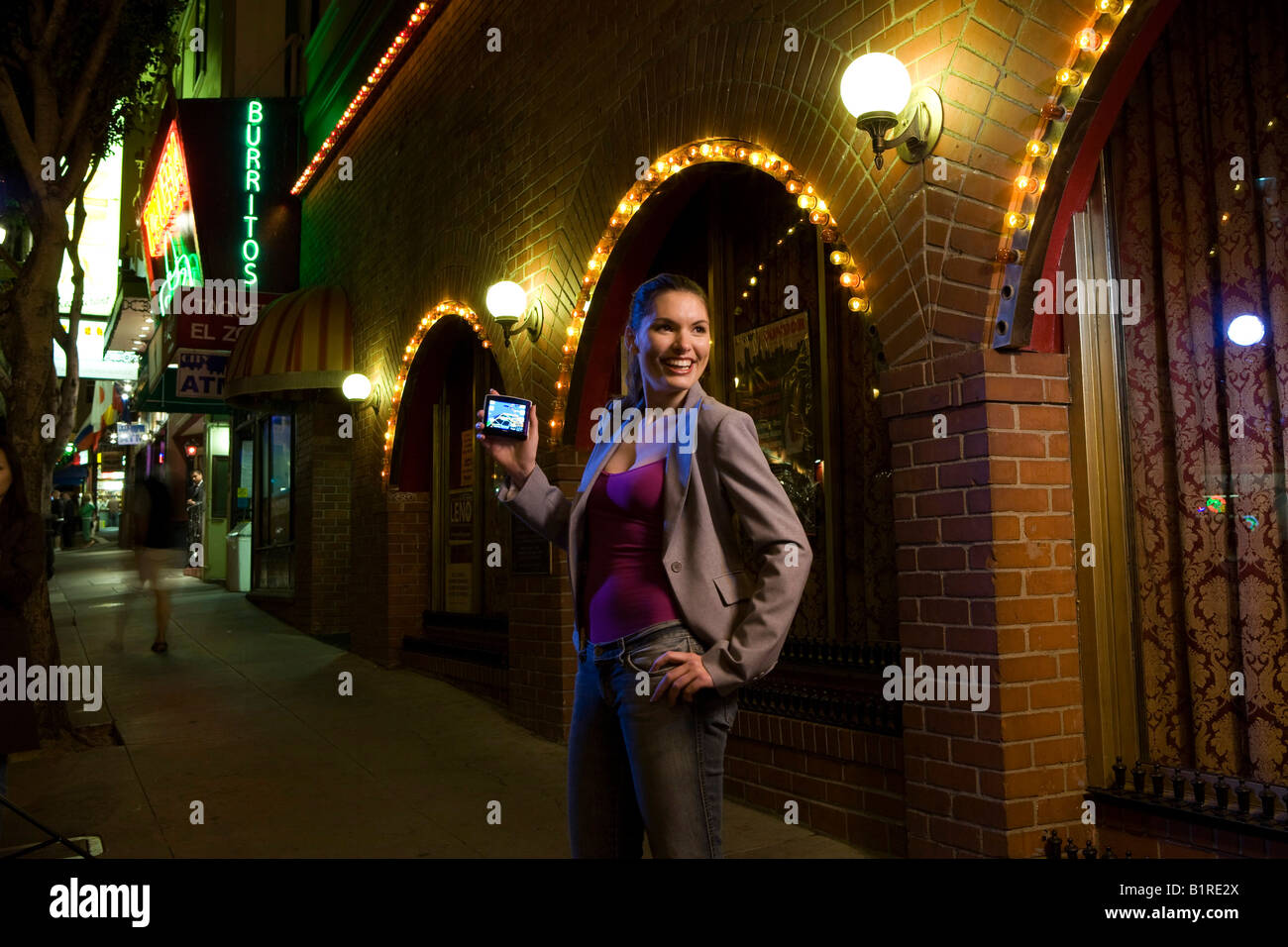 A young woman stands in a well lit street at nightfall carrying a hand held device. - Stock Image