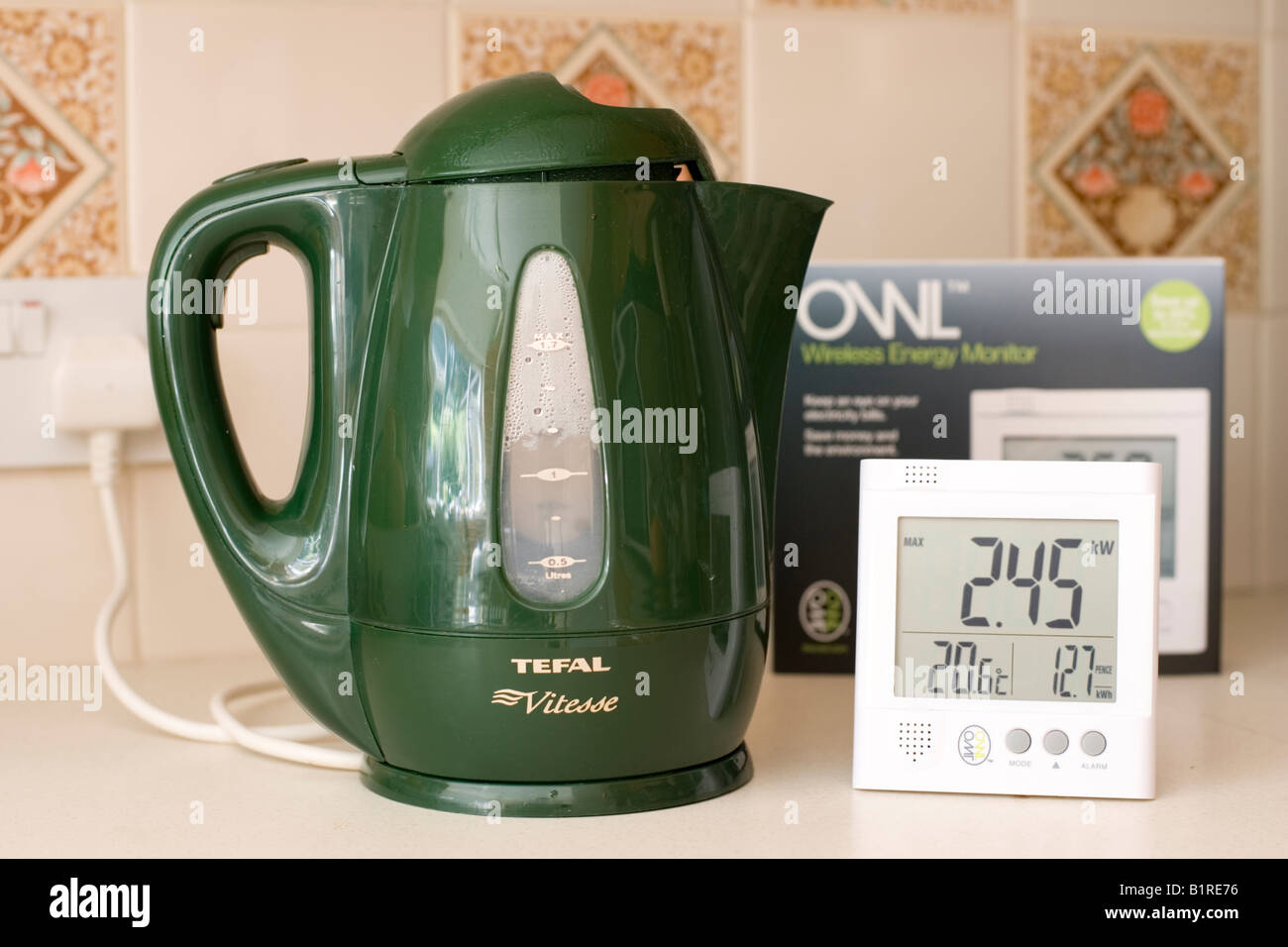 Owl energy monitor measuring electricity use of green kettle UK - Stock Image