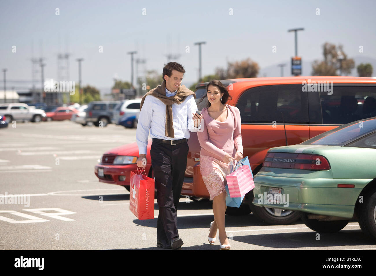A young couple walking through a parking lot filled with cars carrying a hand held device and several shopping bags. - Stock Image