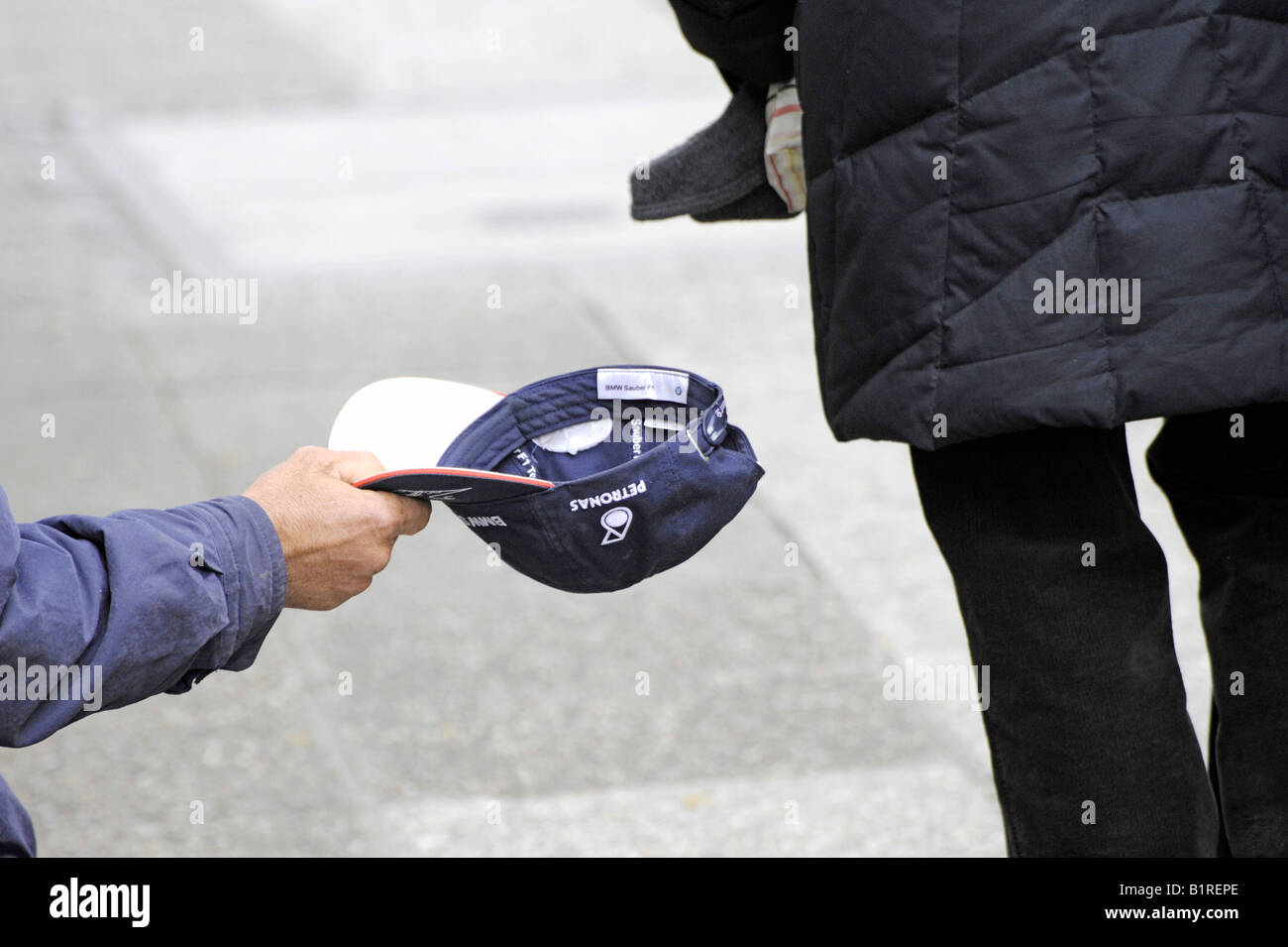 Beggar holding out his cap to collect money, Augsburg, Bavaria, Germany, Europe - Stock Image