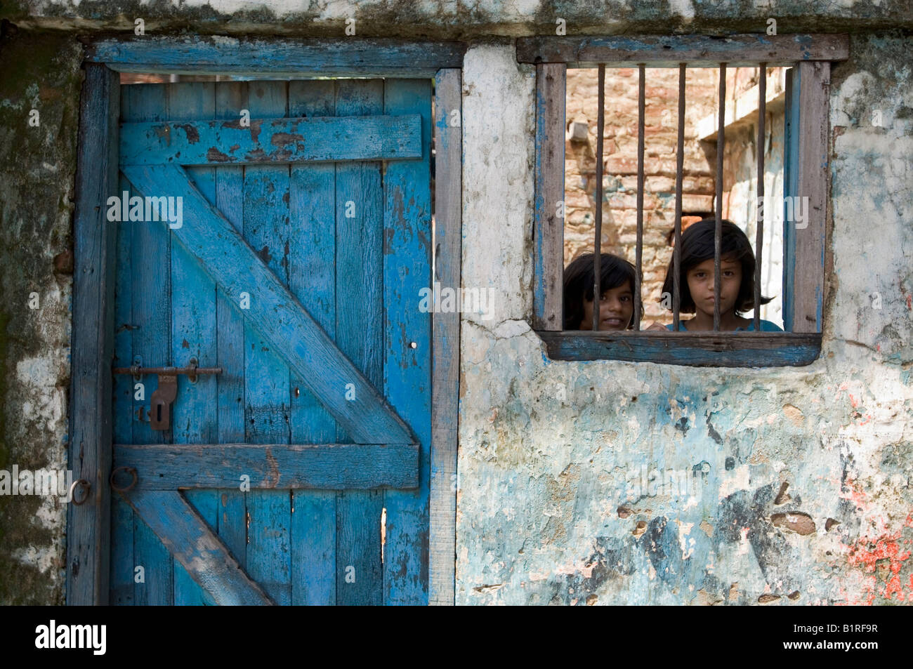 Two girls looking through a barred window in the Pilkana slums, Howrath, West Bengal, India - Stock Image