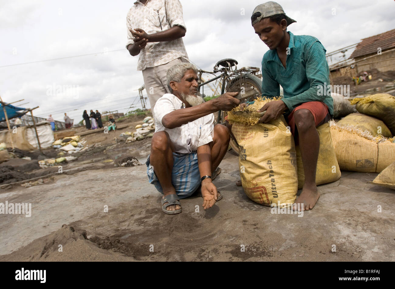 Indian day labourer using sorting copper splinters from toxic industrial slag, earning a living from recycling waste - Stock Image
