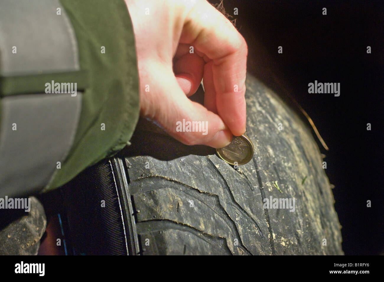Police officer testing the tread depth of a worn car tire, car accident of a vehicle with four completely worn out - Stock Image