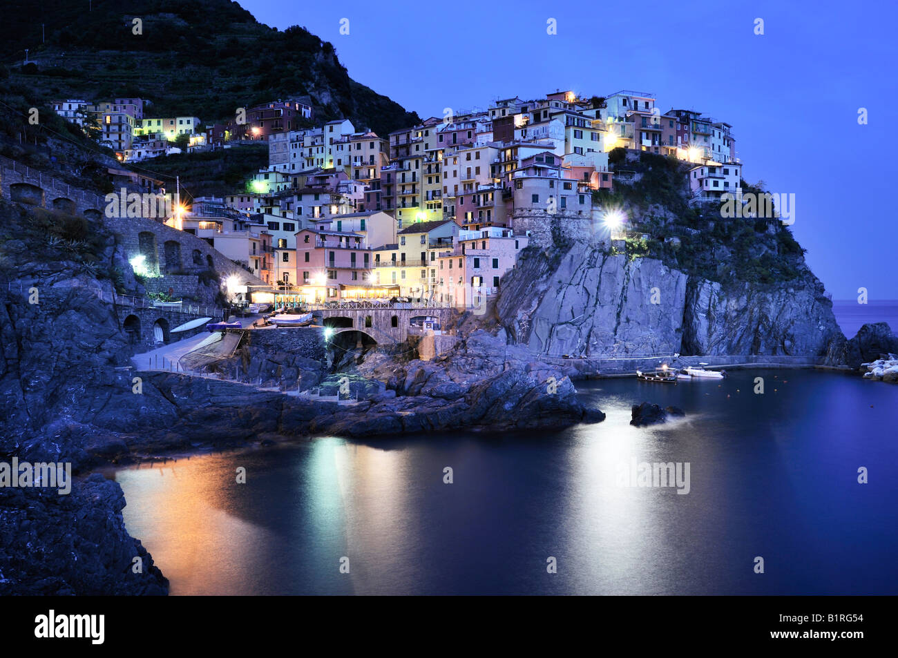 Village of Manarola nestled atop steep coastline at dusk, Liguria, Cinque Terre, Italy, Europe - Stock Image