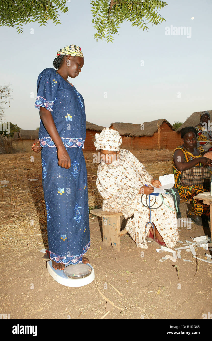 Pregnant woman on a weighing scale at a preventive medical examination, Houssere Faourou, Cameroon, Africa - Stock Image