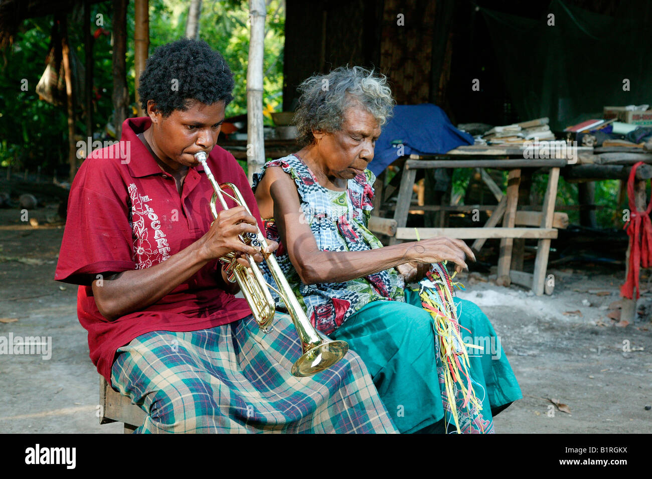 Trombone player sitting next to an old woman, Heldsbach, Papua New Guinea, Melanesia - Stock Image
