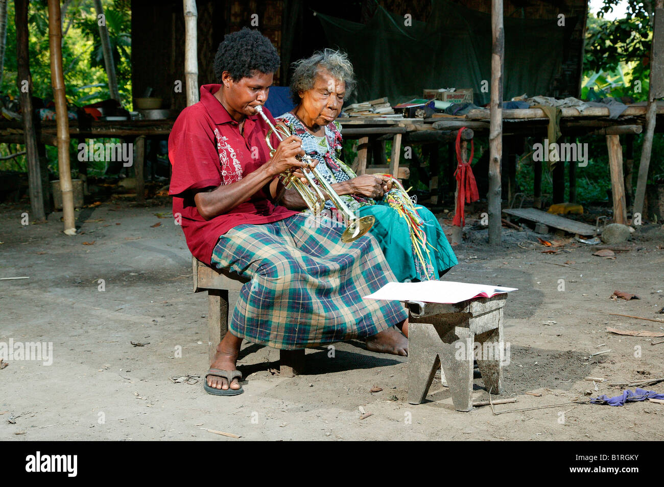 Trumpet player sitting next to an old woman, Heldsbach, Papua New Guinea, Melanesia - Stock Image