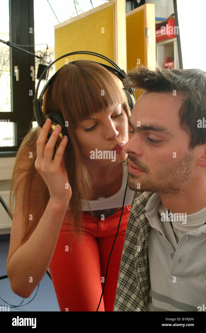 Young woman wearing headphones kissing her sound engineer on the cheek Stock Photo