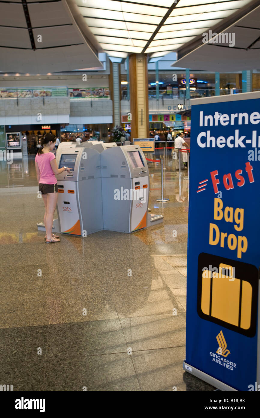 Young woman using the self check-in terminal in the departures hall of Changi Airport, Singapore, Southeast Asia - Stock Image