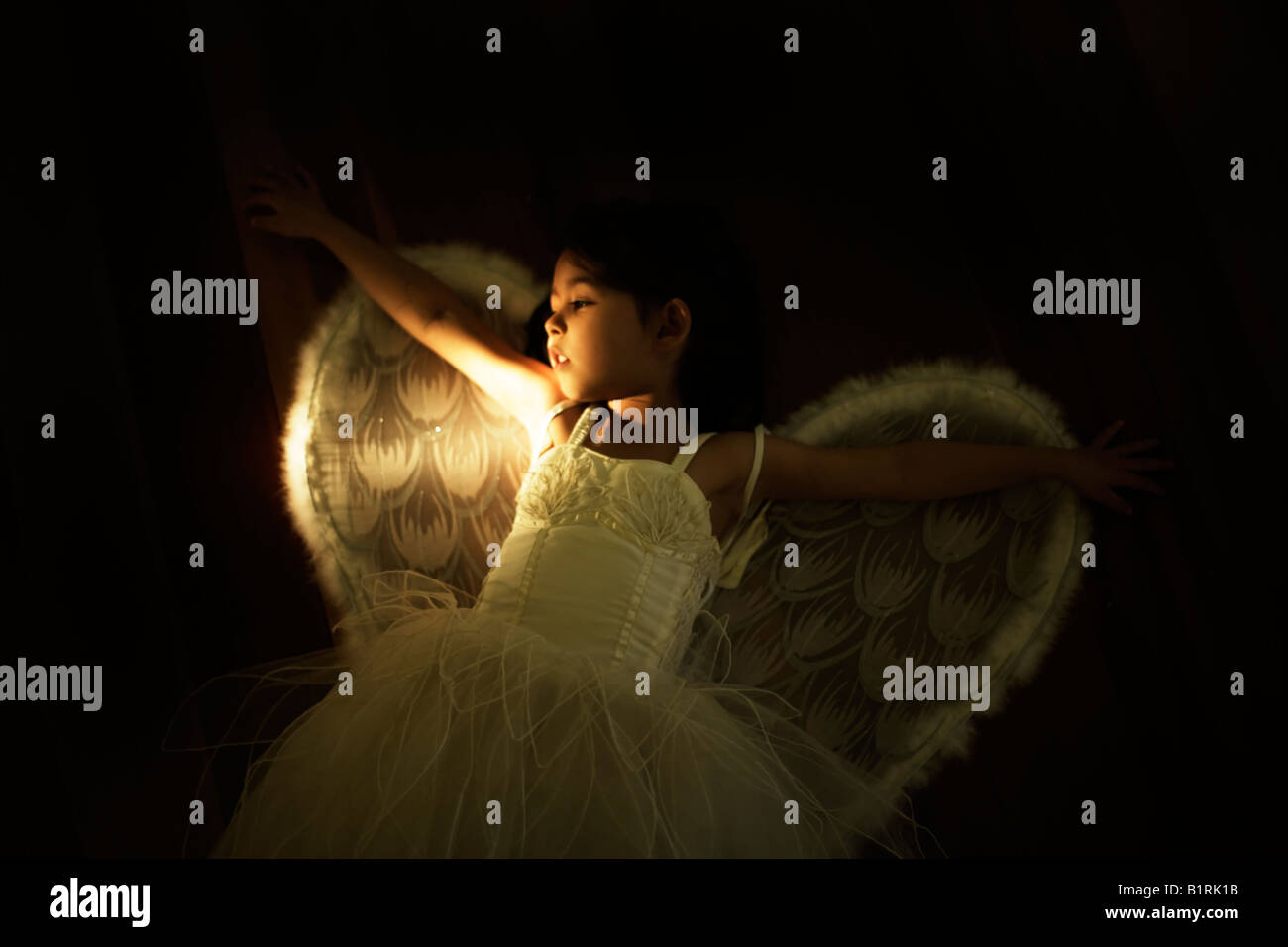 Girl aged four in angel costume lit from side by flashlight - Stock Image