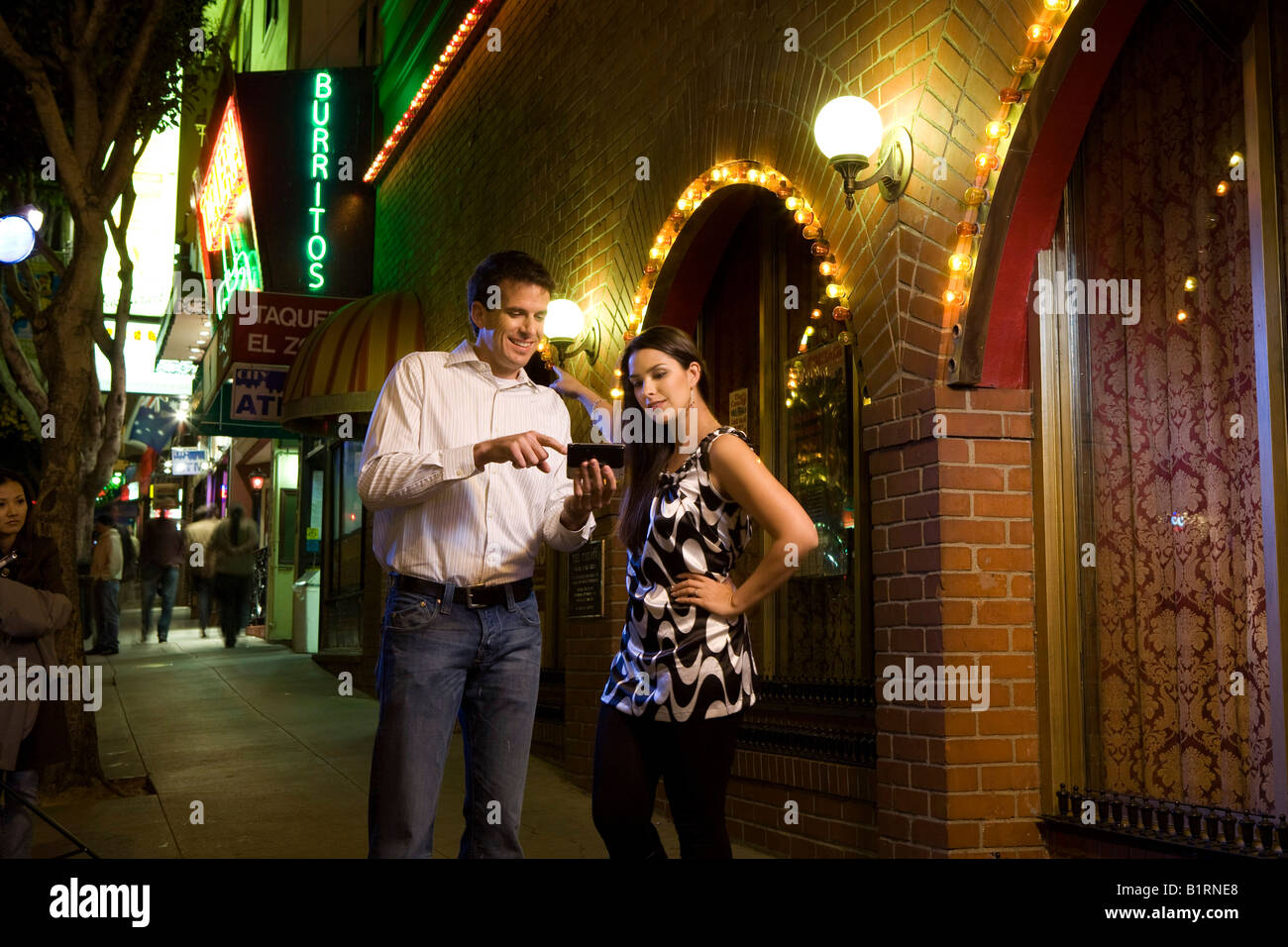 A young man and woman stand in a well lit street at nightfall carrying a hand held device. - Stock Image
