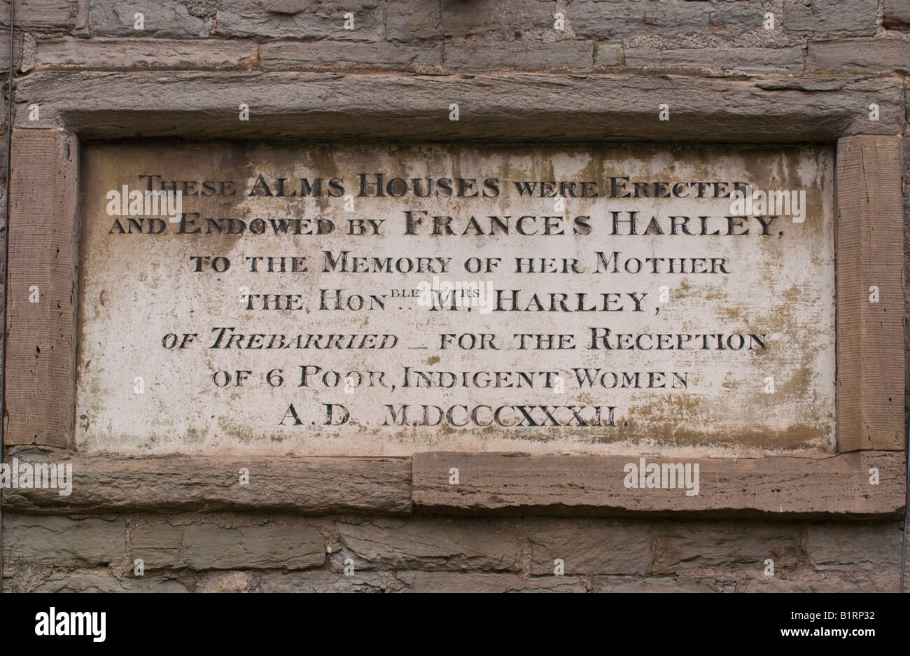 Plaque on outside of Harley Alms Houses built in 1832 for indigent ladies in Hay on Wye Powys Wales UK EU - Stock Image