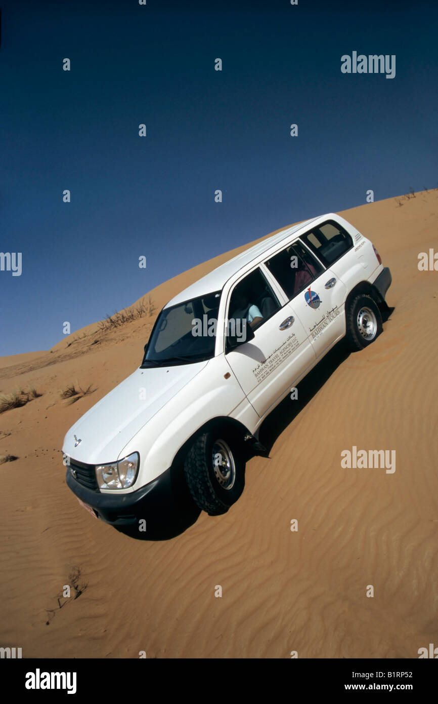 Toyota Land Cruiser, sport utility vehicle, SUV, driving down a sand dune, Wahiba Sands, Oman, Arabian Peninsula, - Stock Image