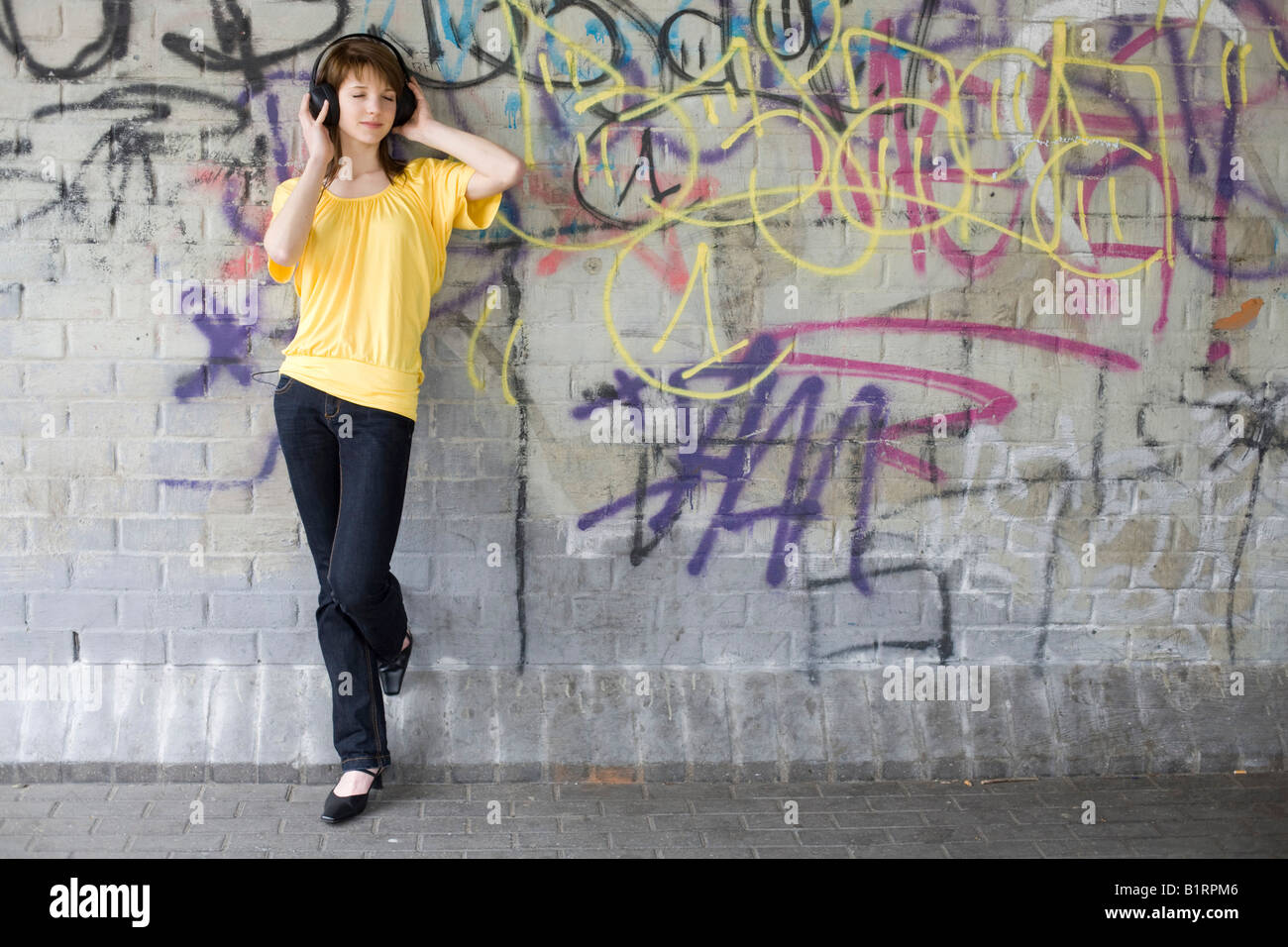 Young woman listening to music with big headphones, standing in front a graffiti sprayed wall - Stock Image