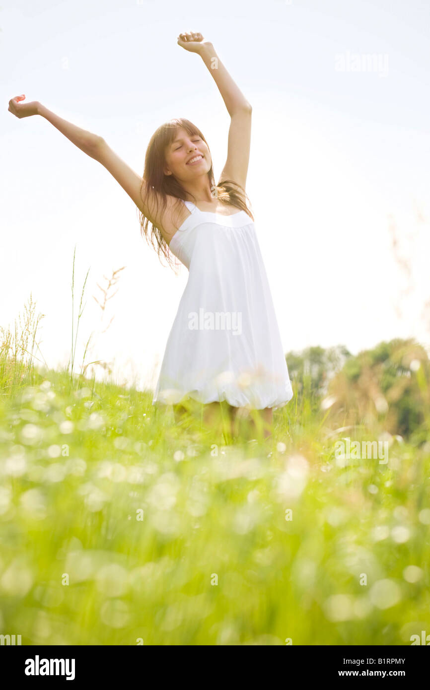 Young, dark-haired woman wearing a white dress, spinning around with outstretched arms on a summerly meadow - Stock Image