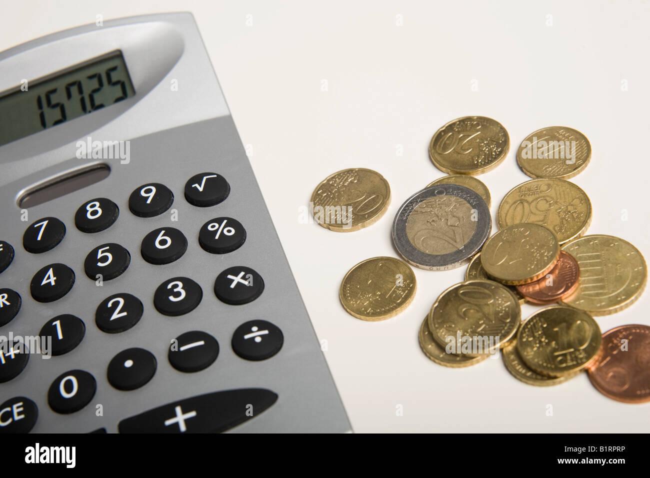 Euro coins next to a calculator - Stock Image