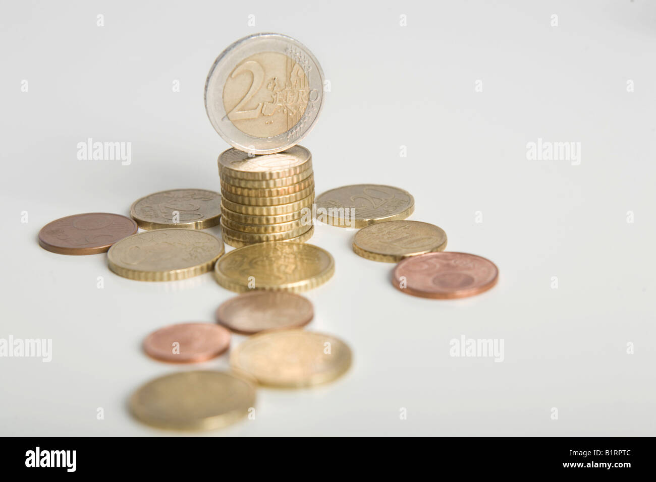Stacked Euro coins and other coins lying on a table - Stock Image