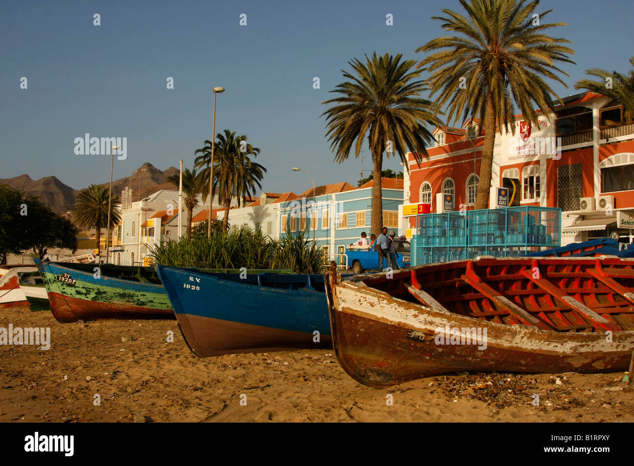 Rowboats pulled onto the beach in front of the coastal promenade of Mindelo on Sao Vicente Island, Cape Verde Islands, - Stock Image