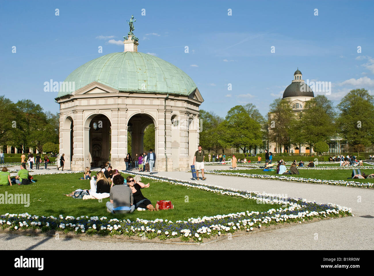 People enjoying the warm spring day in front of the pavilion for the goddess Diana in the Hofgarten, Munich, Bavaria, Stock Photo