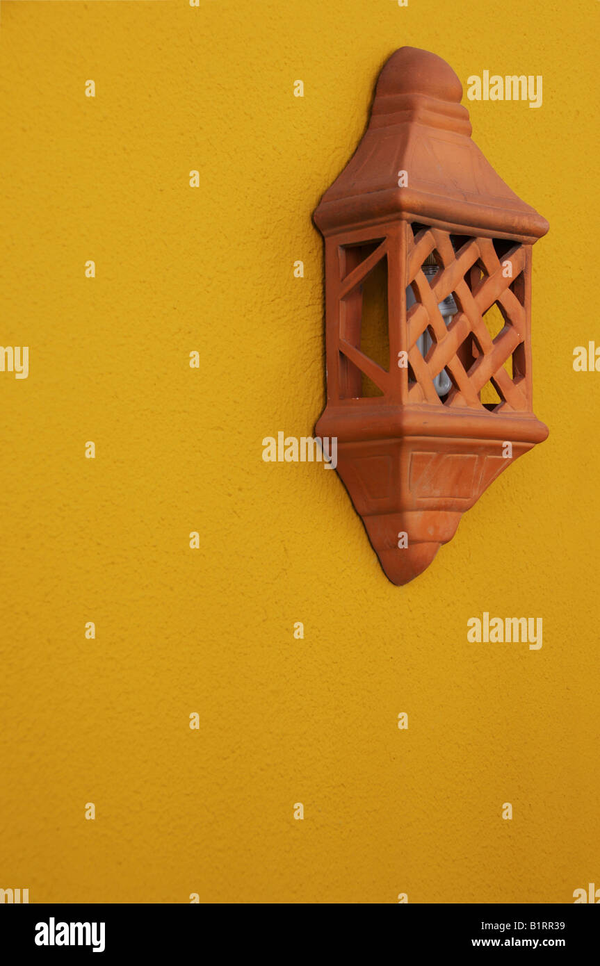Terracotta lamp on a yellow wall, Seville, Andalusia, Spain, Europe Stock Photo