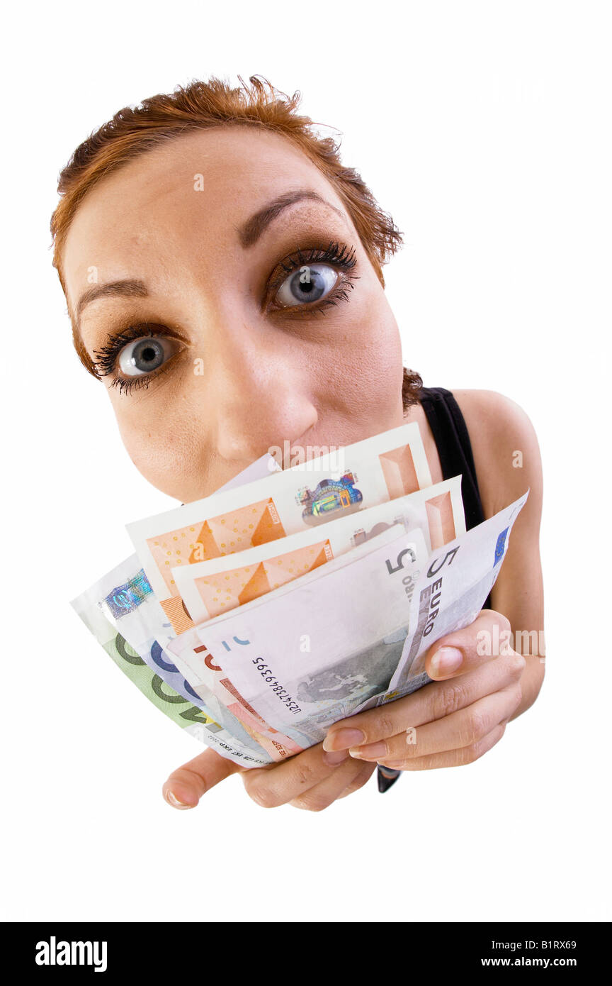Woman holding banknotes in front of her nose, fish-eye lens - Stock Image
