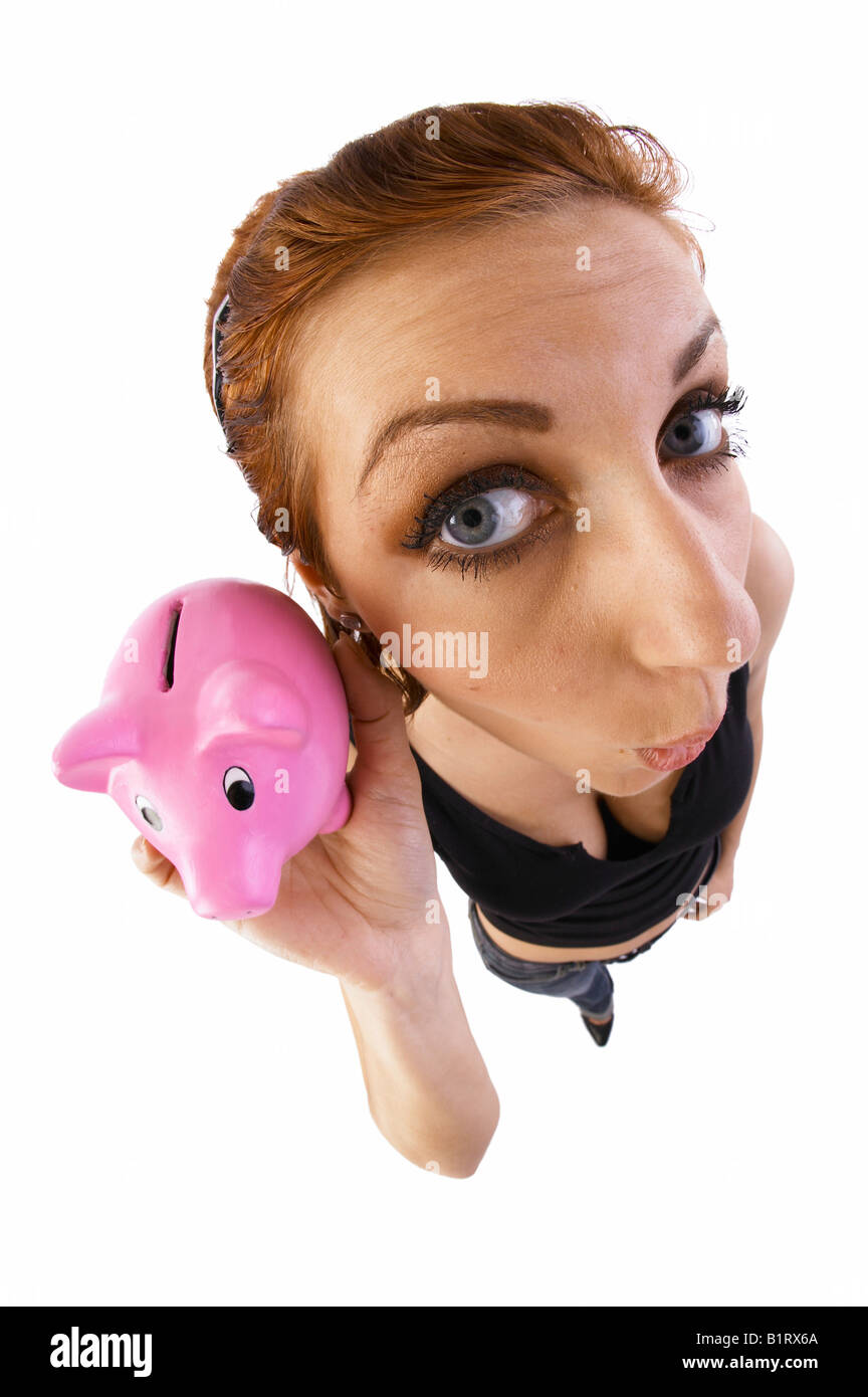 Woman holding a piggy bank to her ear, fish-eye lens - Stock Image