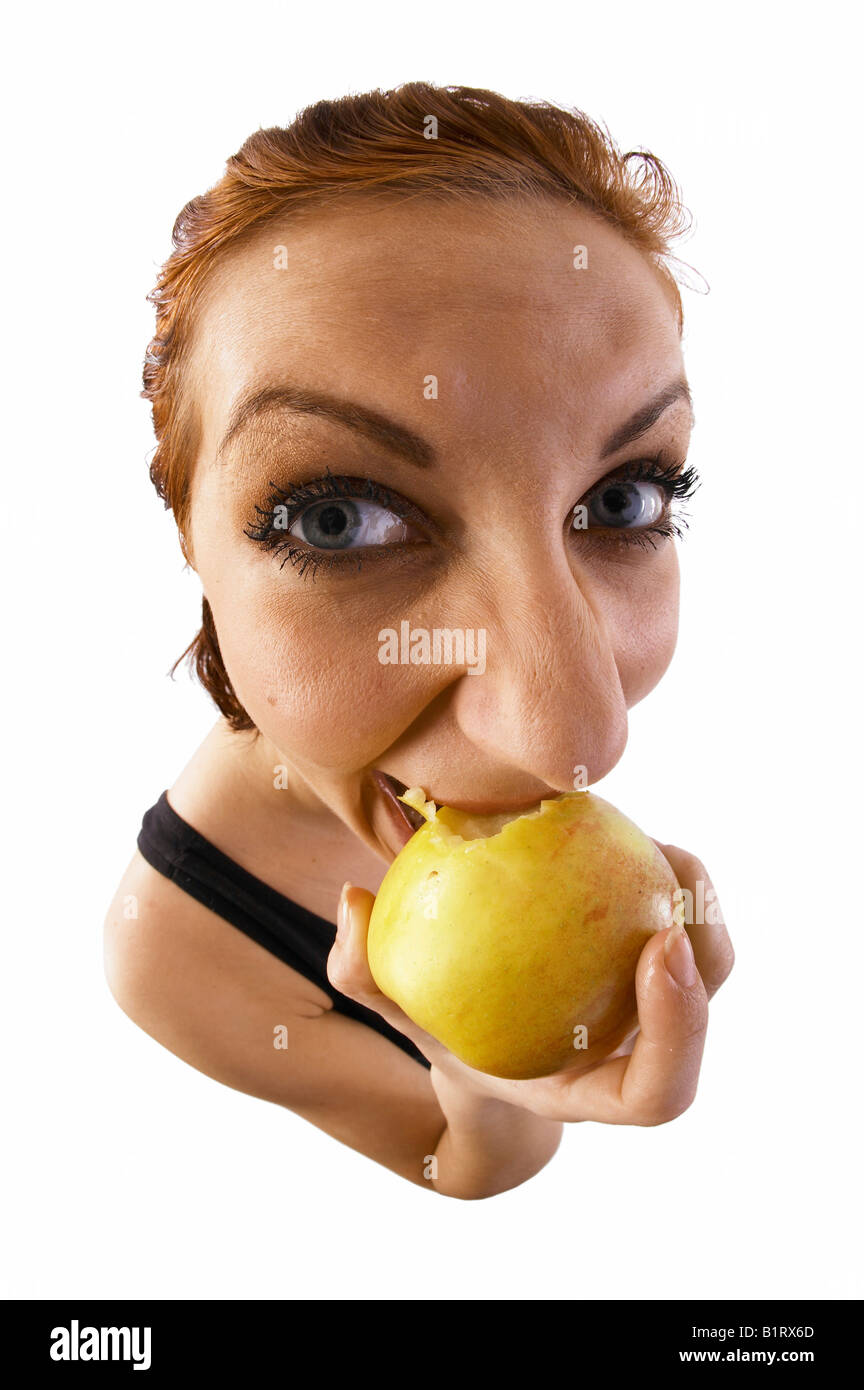 Woman biting into an apple, fish-eye lens - Stock Image