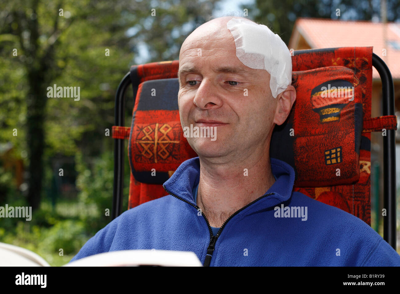 Man, 45, with an adhesive bandage on his head, sitting in a garden chair reading a book, Geretsried, Bavaria, Germany, Stock Photo