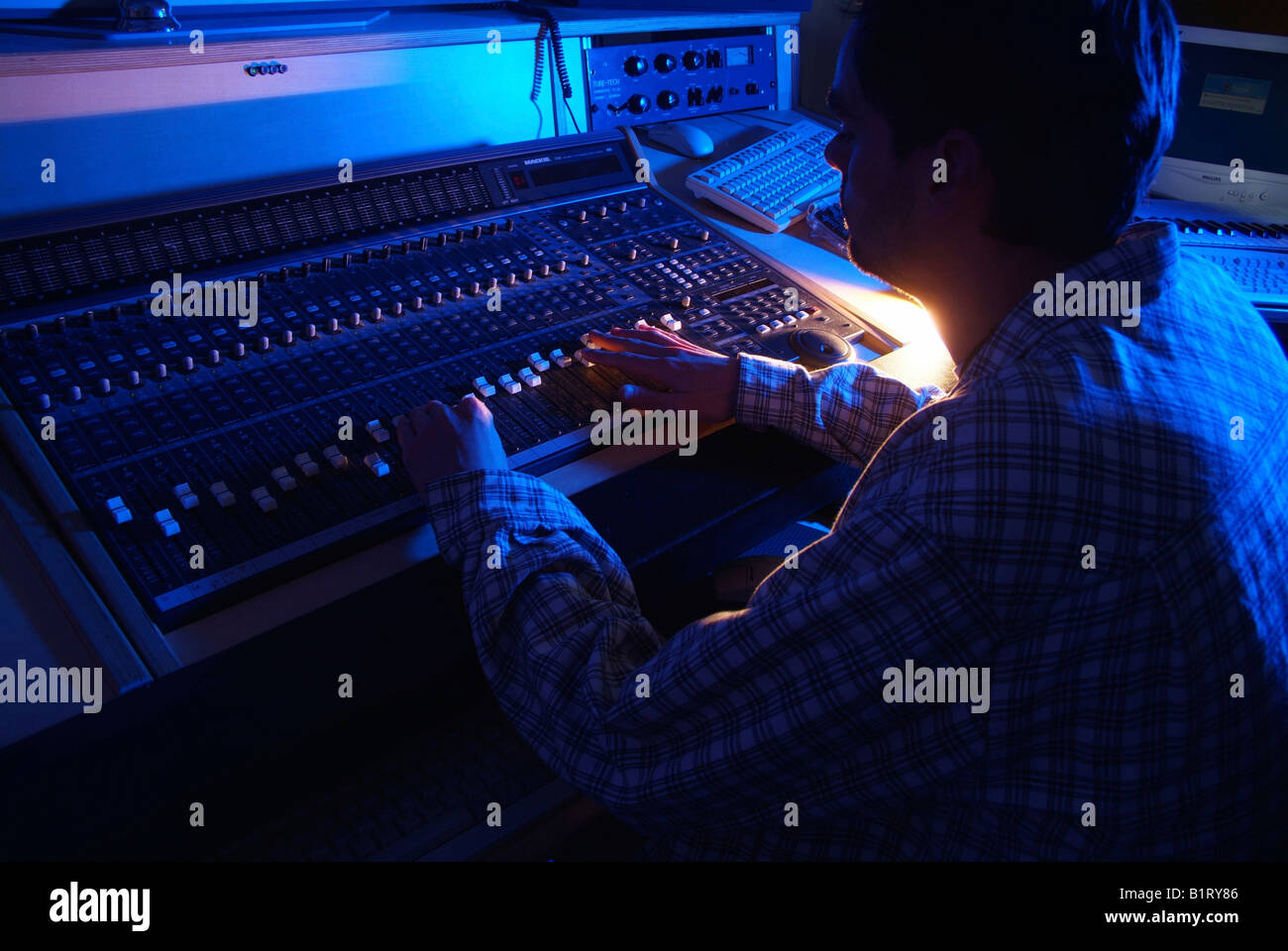 Sound engineer working on a mixer unit of a recording studio Stock Photo