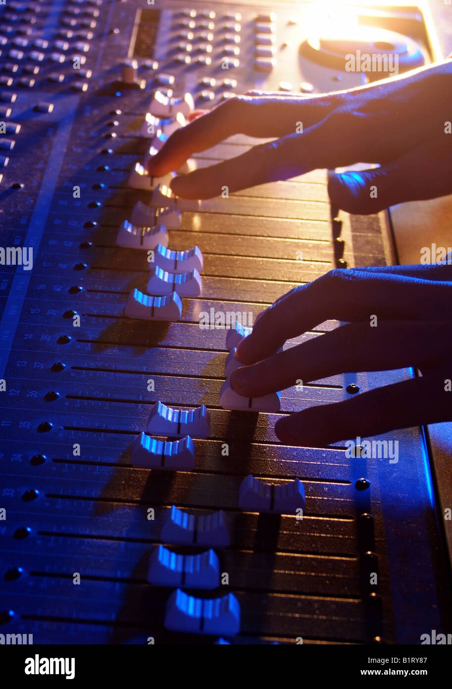 Hands of a sound engineer adjusting the regulators of a professional mixer unit Stock Photo