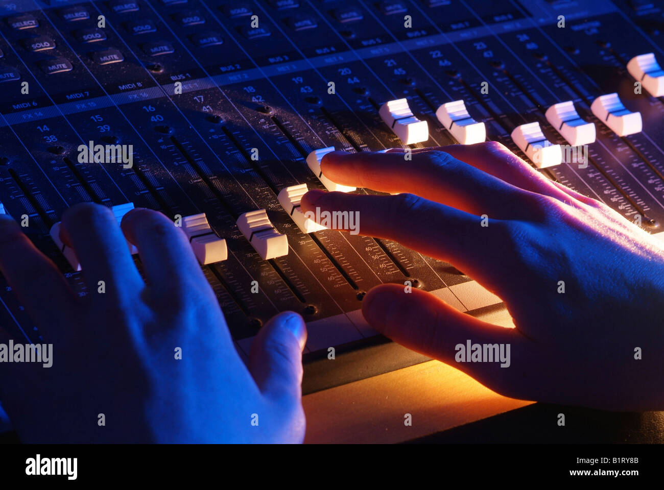 Hands of a sound engineer adjusting the regulators of a professional mixer unit - Stock Image