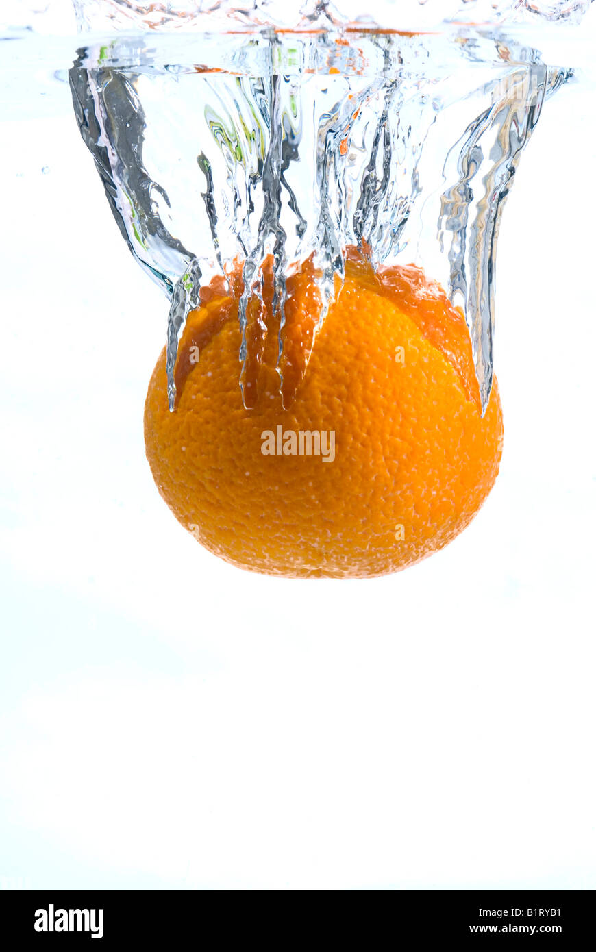 Orange plunging into water - Stock Image
