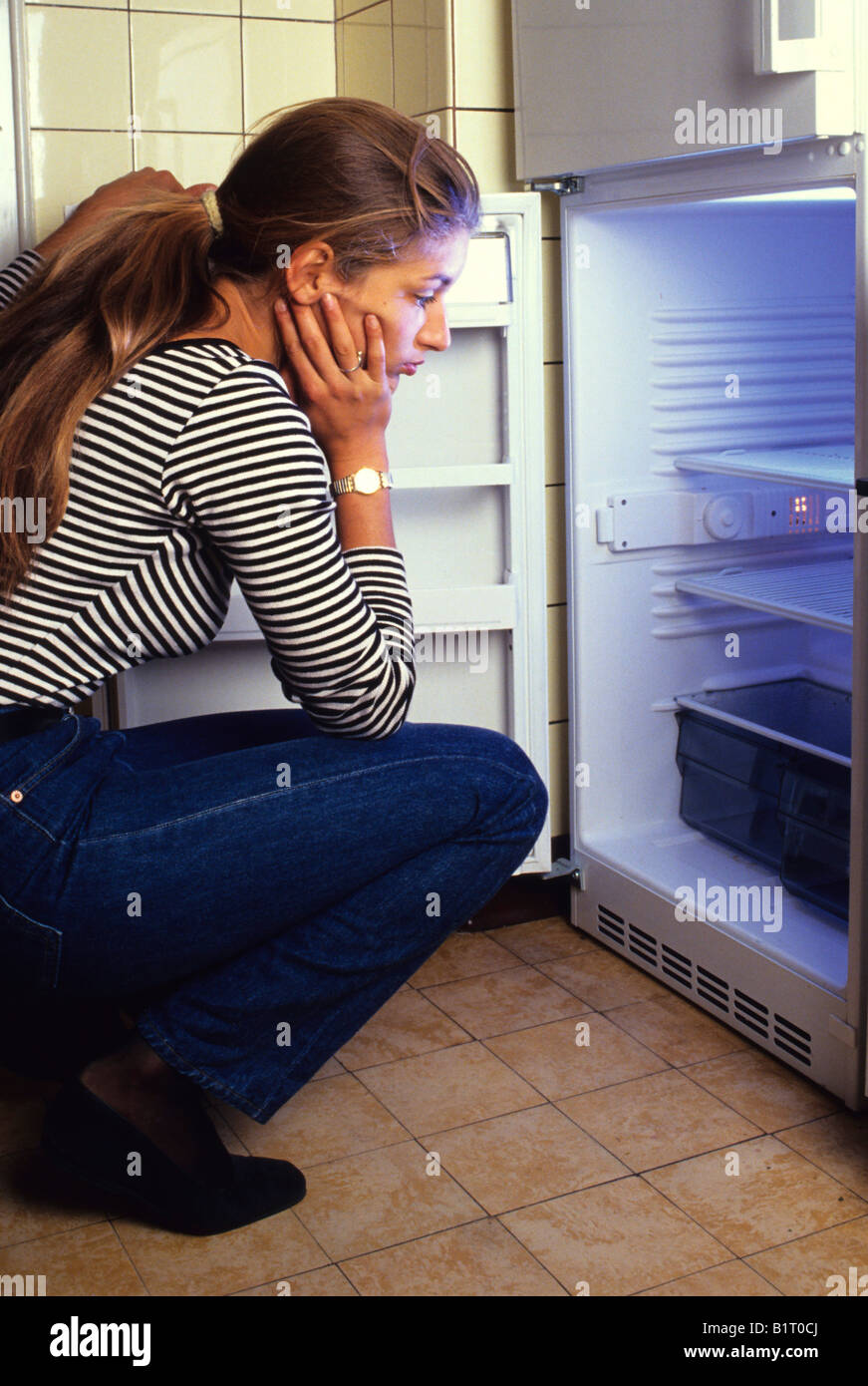 Woman looking into an empty fridge - Stock Image