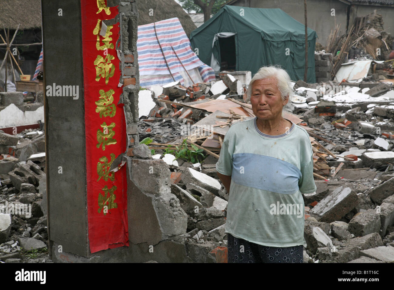 Old lady stands in front of what used to be her house in Mianzhu following the Sichuan Earthquake of 12th May 2008, - Stock Image