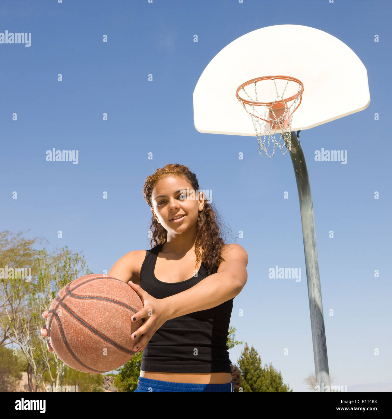 A teen with a basketball hangs out at the court - Stock Image
