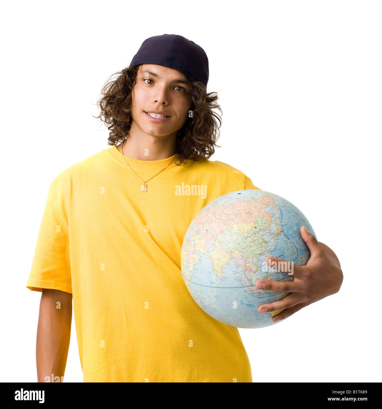 A teenage boy holds a globe and smiles - Stock Image