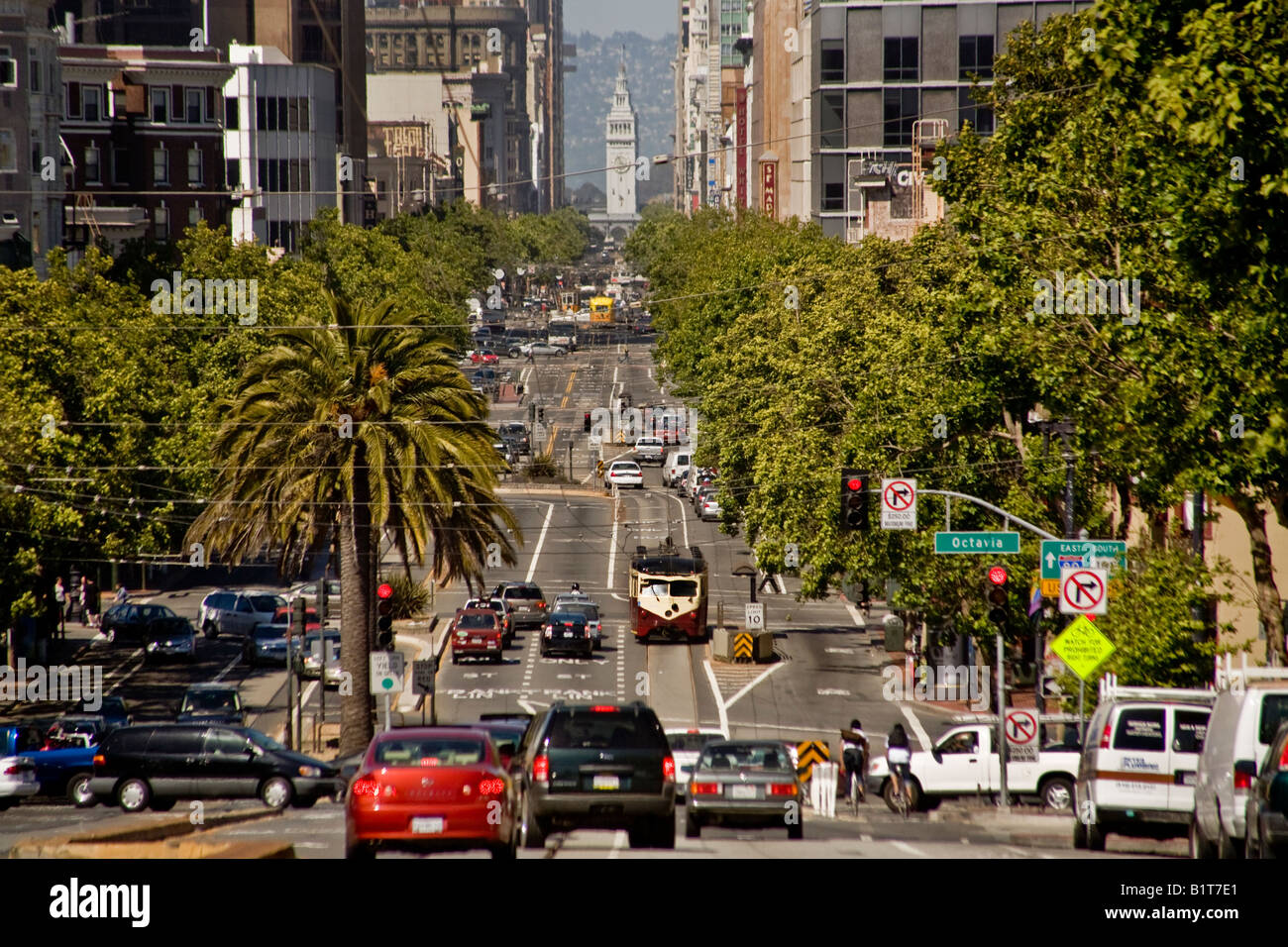 Trolleys mix with regular traffic on Market Street in San Francisco Note the Ferry Building in background - Stock Image