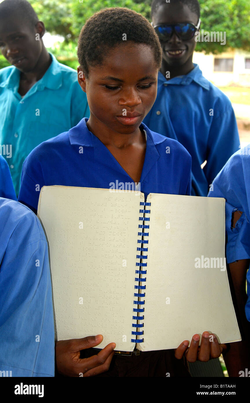 A female student of the Akropong School for the Blind shows a text book written in Braille script, Akropong, Ghana - Stock Image