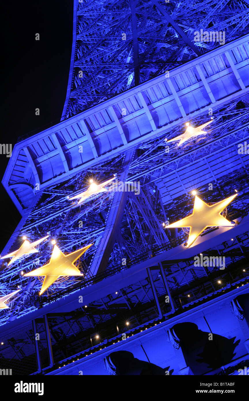 The Eiffel tower illuminated with the yellow and blue colours of the European Union flags in Paris, France. - Stock Image