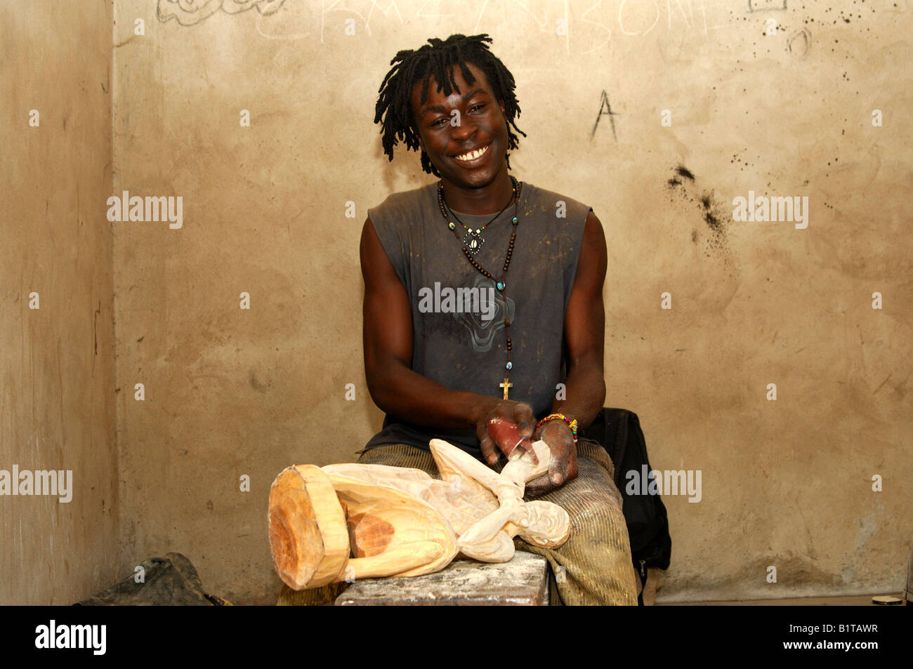 Smiling young wood carver with Rasta look polishing a wood sculpture at the carving centre in Aburi, Eastern Region, - Stock Image