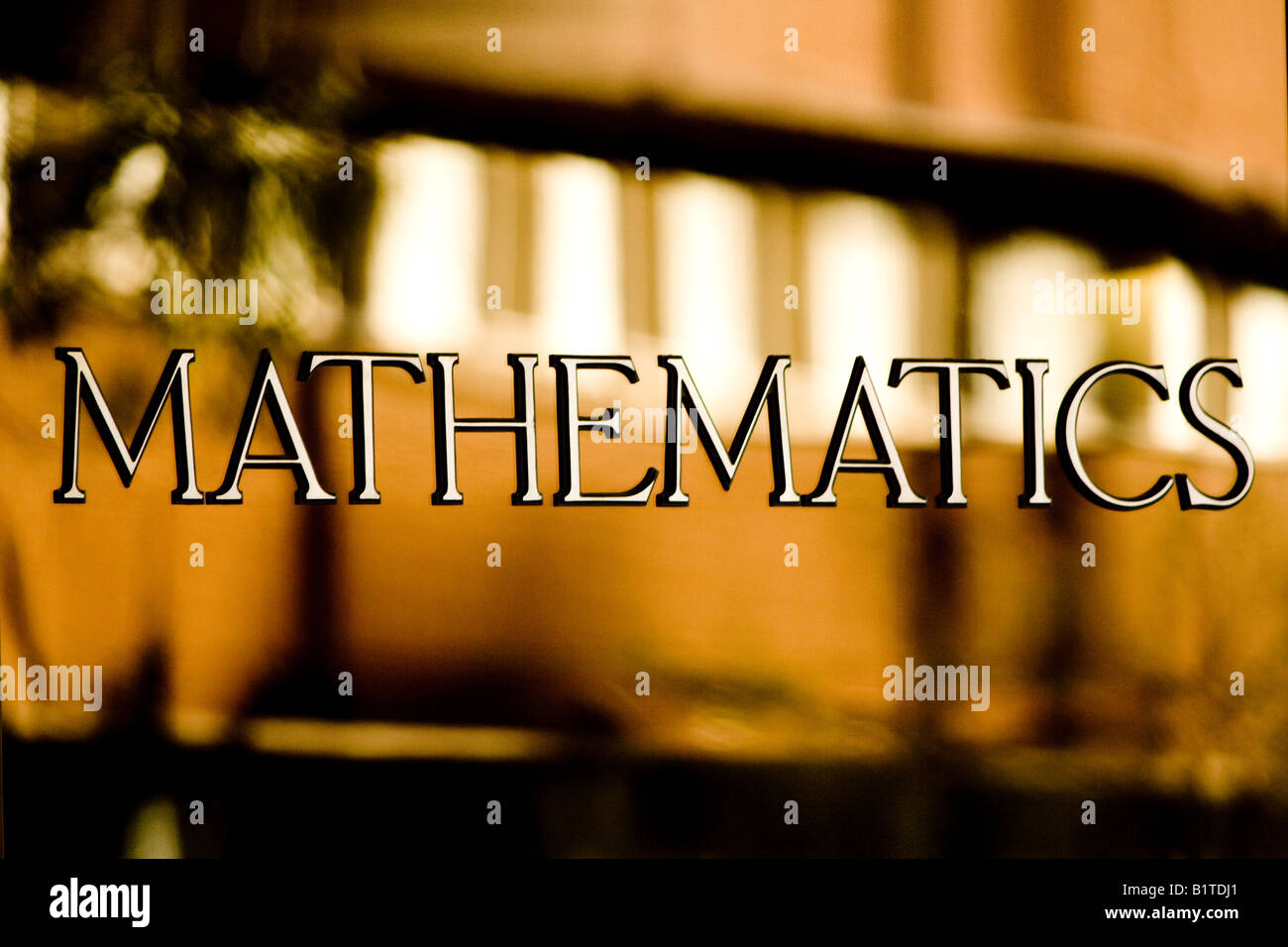 Mathematic sign on door of building of higher learning. Stock Photo