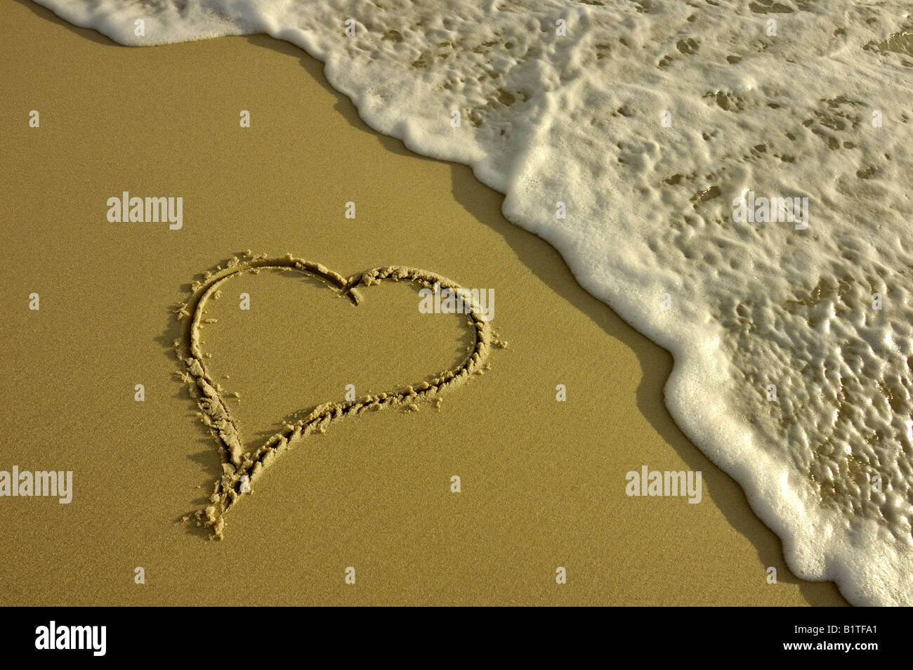 A heart drawn in the sand about to be washed away by a wave. Taken in the low light of evening. - Stock Image